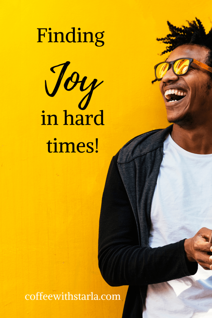 Finding Joy in Hard Times, Yellow wall with happy black man wearing sunglasses, white t-shirt and a black jacket