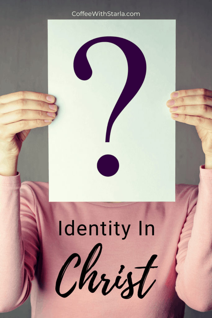 My identity in Christ, woman holding a question mark on a paper in front of her face.